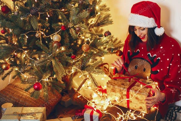 Happy woman in santa hat opening gift box at christmas tree lights