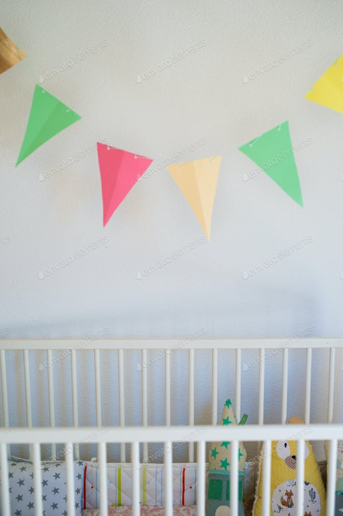 Cot in bedroom decorated for newborn baby