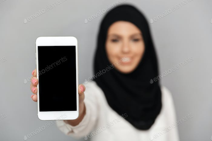 Blurry image of smiling muslim woman 20s in islamic headscarf wi