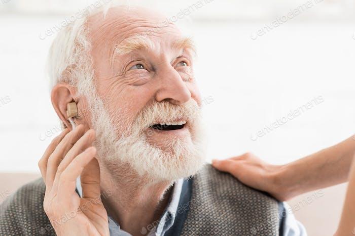 Froh Mann mit Hörgerät im Ohr, wegzuschauen
