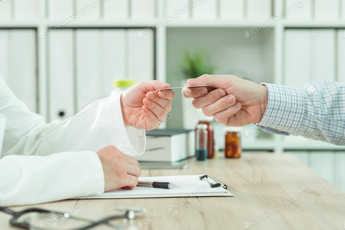 Doctor taking medical insurance card from patient