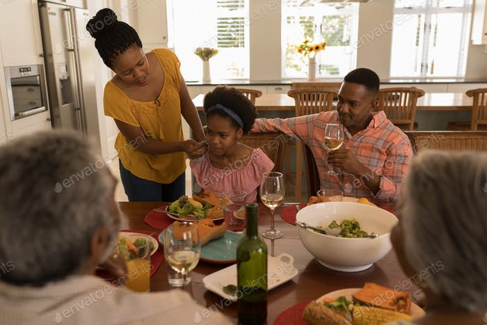 Mother wiping daughters mouth with napkin after meal on dining table at home