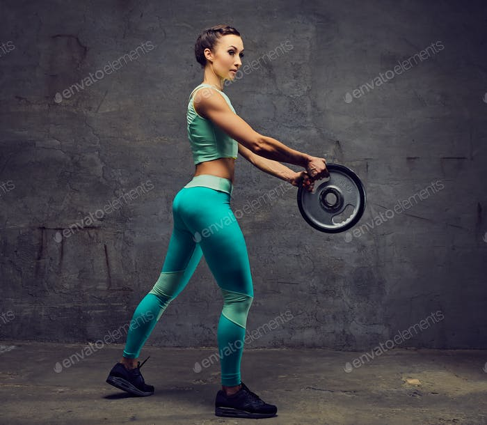 Sporty female working out with barbell weight over grey background.
