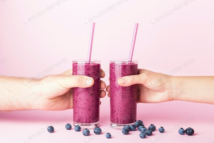 Woman`s and Man`s Hands Holding Glasses of Blueberries Smoothie.