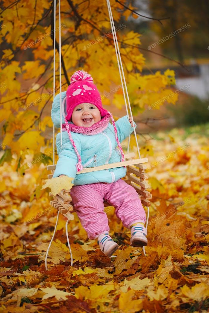 little girl on swings in autumn park