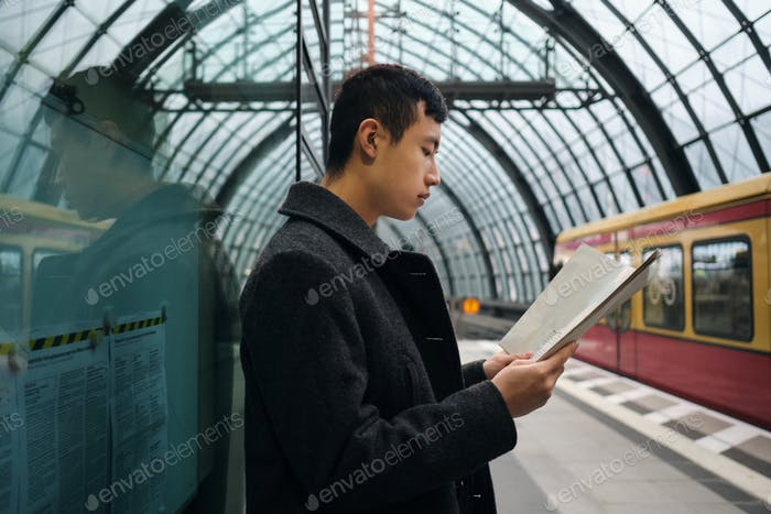 Side view of young Asian businessman intently reading newspaper while waiting train at metro station