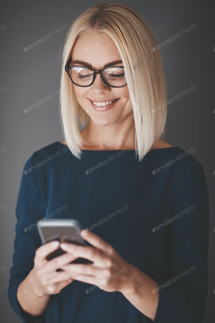 Smiling young businesswoman using her cellphone against a gray background