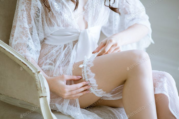 Beautiful sexy lady in elegant white robe and garter.