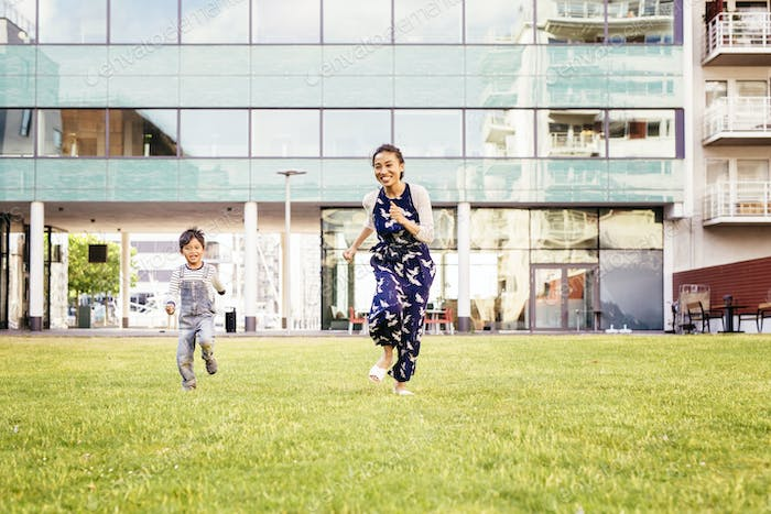 Mother running with son (4-5) on grass