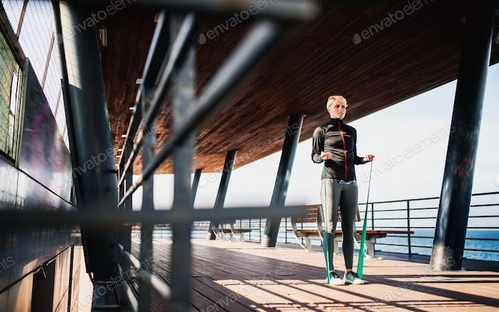 Eine junge Sportlerin macht Bewegung auf dem Seeweg