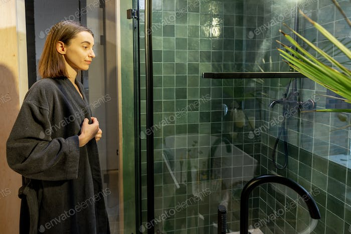 Woman takes off her robe and goes to the shower