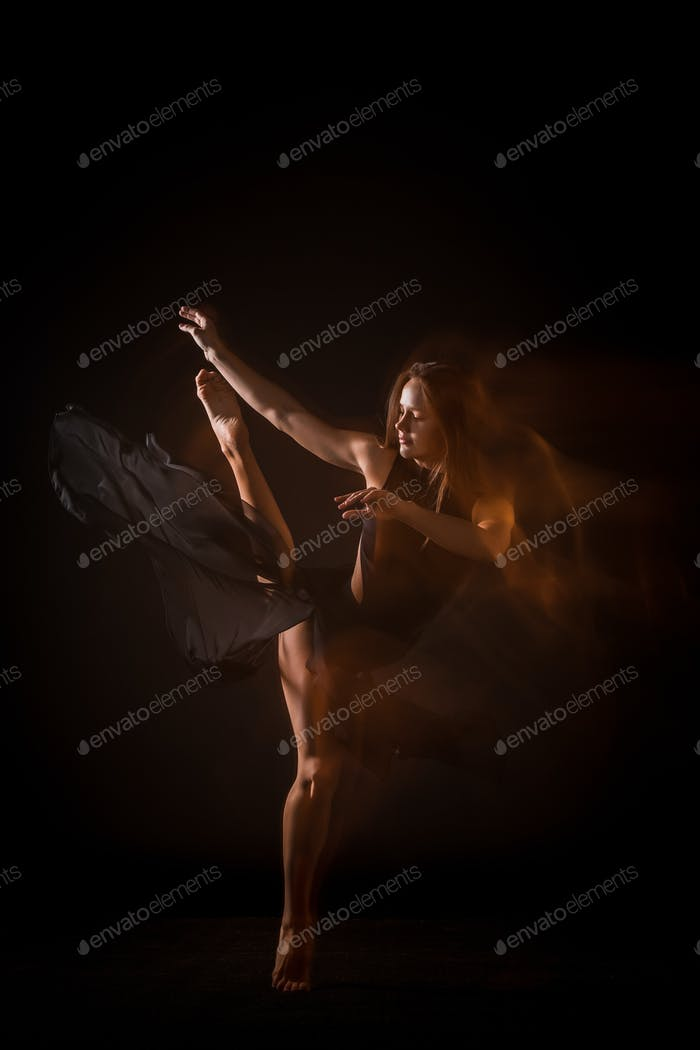 Young beautiful dancer dancing on black background