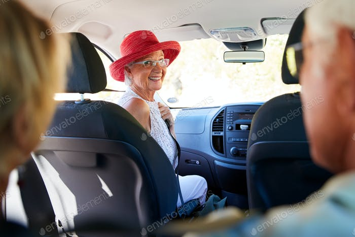 Group Of Senior Friends Sitting In Car Driving To Vacation