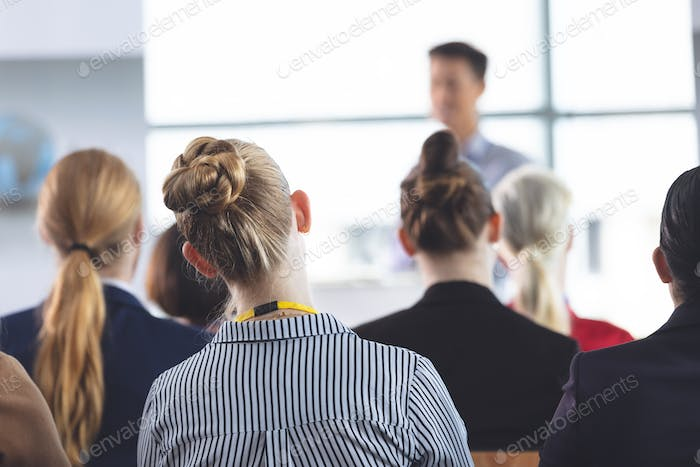 businesswoman listening to businessman speak at business seminar in office building
