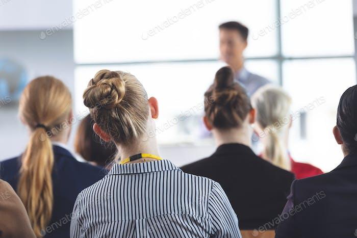 Geschäftsfrau hören Geschäftsmann sprechen auf Business-Seminar im Bürogebäude