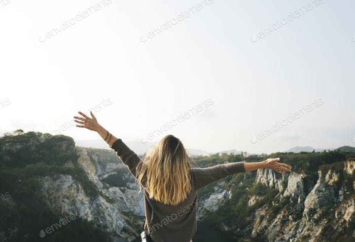Carefree woman arms outstretched on the mountain