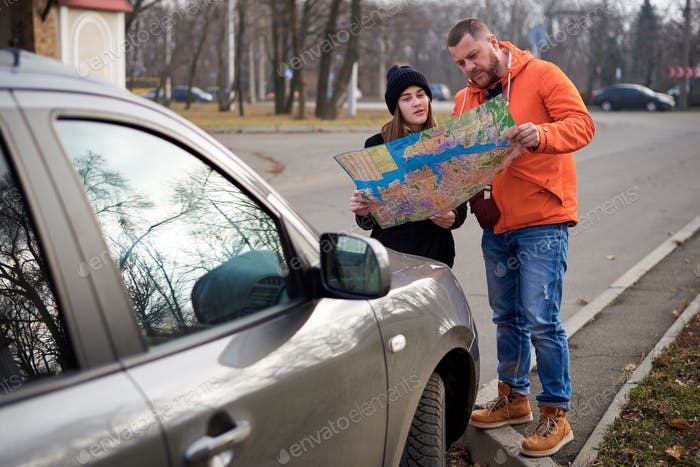 Young couple with a map near a car on the road