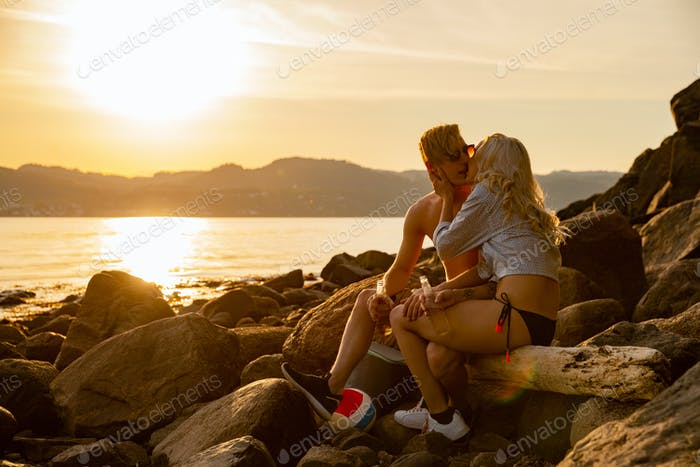 Beautiful Couple Kissing And Drinking Beer While Sitting On Rocks