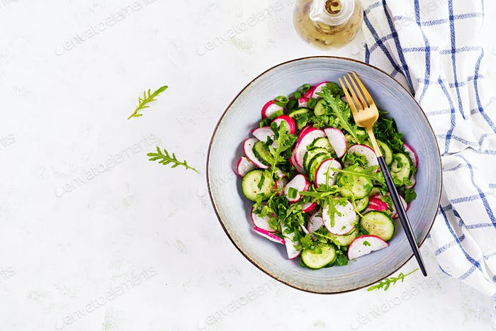 Vegetarian vegetable salad of radish, cucumbers, arugula and green onions