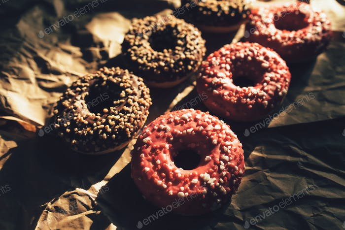 Fresh chocolate and raspberry donuts on crumpled craft paper