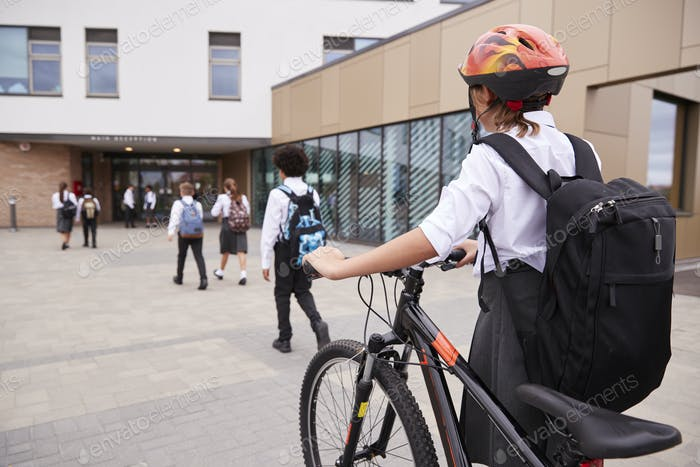 Group Of High School Students Wearing Uniform Arriving At School Walking Or Riding Bikes