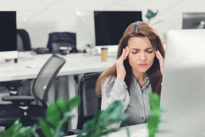 young businesswoman suffering from headache while working in office