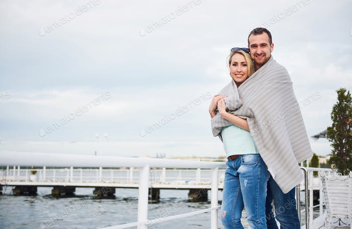 Beautiful young couple embracing, standing on a pier near water