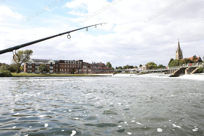 A fishing rod and line over a stretch of water by a weir and bridge, and the buildings of a town.