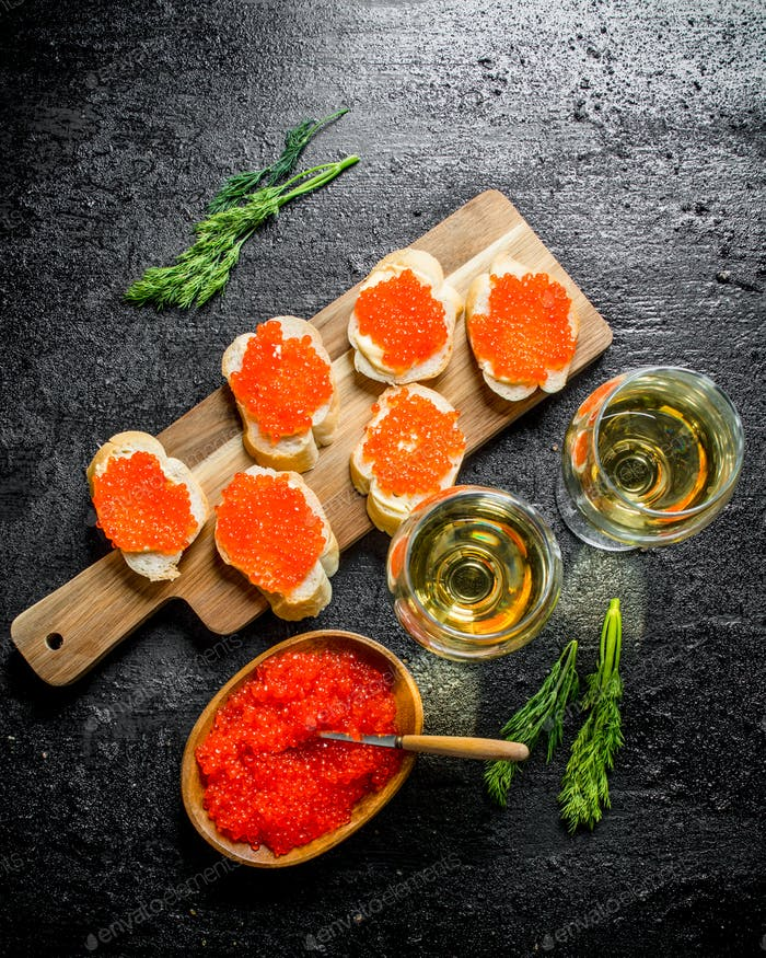 Sandwiches with red caviar on a cutting Board and white wine in glasses.