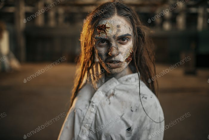 Female zombie walking in abandoned factory, horror