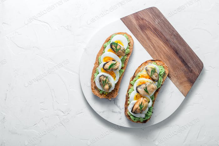 Smoked mussels and avocado toasts, white background, copy space