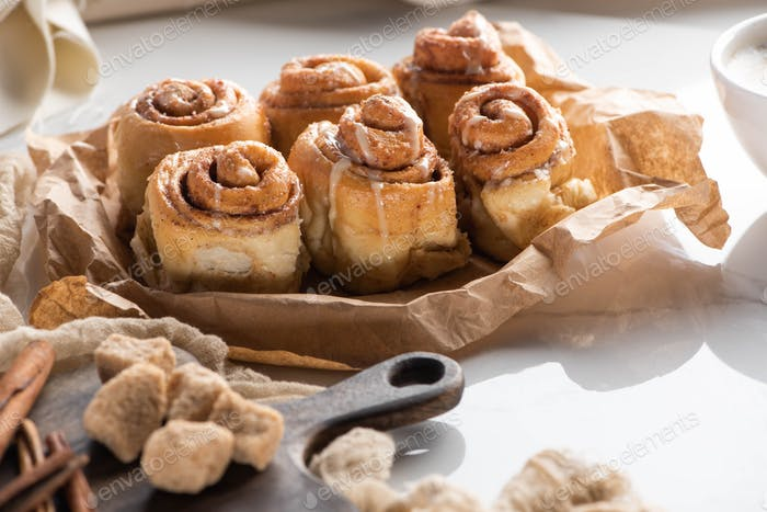 Fresh Homemade Cinnamon Rolls Near Cutting Board With Brown Sugar And Cinnamon Sticks