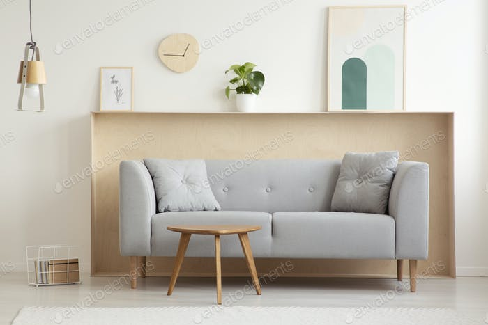 Wooden table in front of grey sofa in simple living room interio