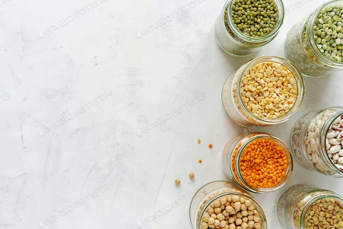 Colorful healthy dried legumes in glass jars