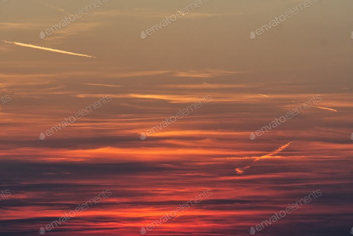 Fiery orange sunset sky with clouds.