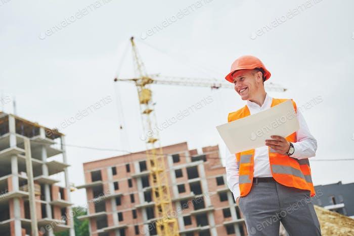 Architektur und Wohnungsrenovierungskonzept - Mann im Helm und Handschuhe mit Bauplan in der Fabrik