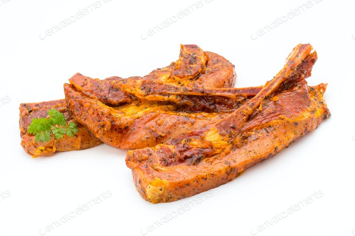 Spicy marinated spare ribs barbecued on the white background.