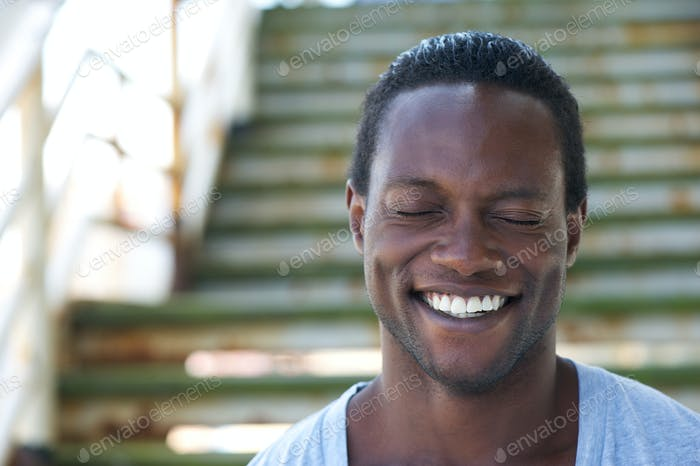 Portrait of an african american man laughing with eyes closed