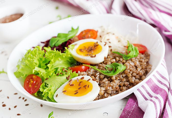 Buckwheat porridge buddha bowls with beetroot, cabbage, boiled eggs and  fresh tomato