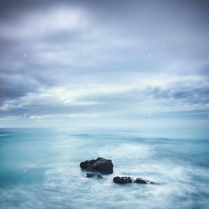 Dark rocks in a blue ocean under cloudy sky in a bad weather.