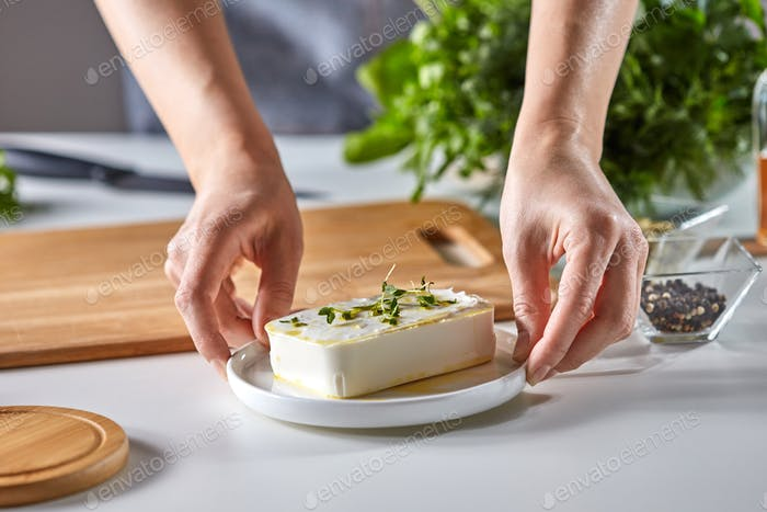 The hands of the girl hold a plate with soft cheese with green sprouts on a white table with dill