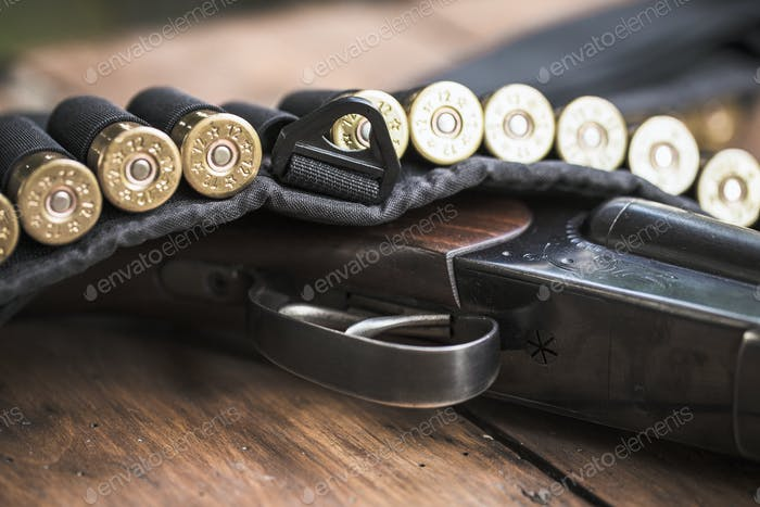 Shotgun with cartridges on a wooden background