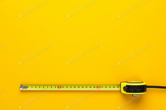 Maßband auf dem gelben Hintergrund