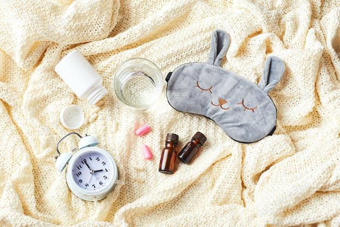 Sleeping mask, alarm clock, earplugs and pills. Healthy night sleep creative concept.