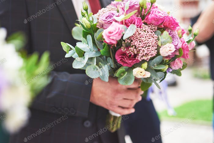 Stylish groom holding a tender pink wedding bouquet