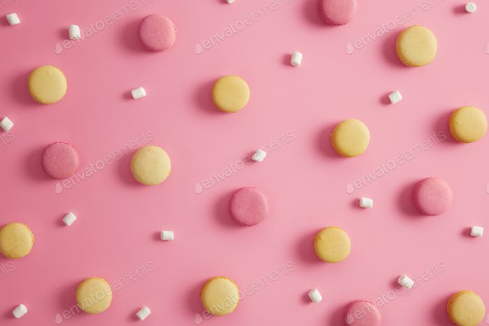 Colored round delicious macaroons and marshmallow on pink pastel background. Tasty french dessert co