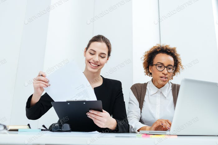 Two happy businesswomen using clipboard and laptop together