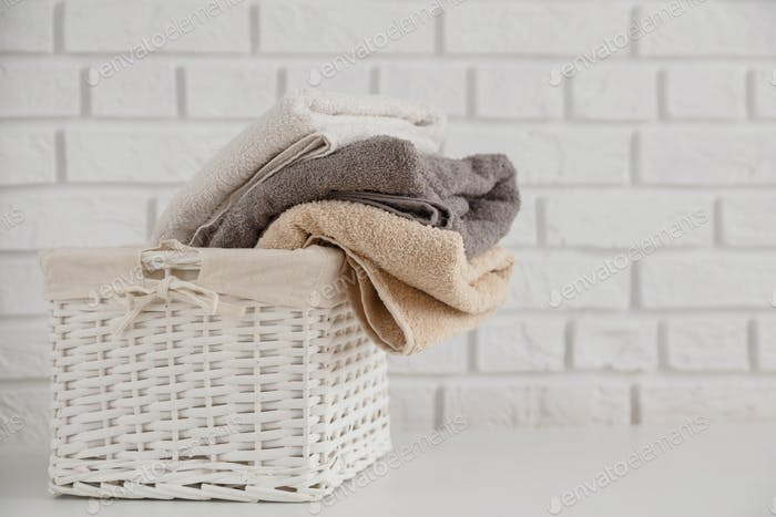 Multicolor fresh towels in wicker straw basket on white table with white brick wall on backdrop.