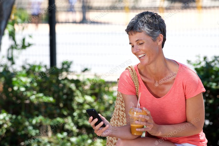 happy mature woman sitting outdoors with drink and using mobile phone