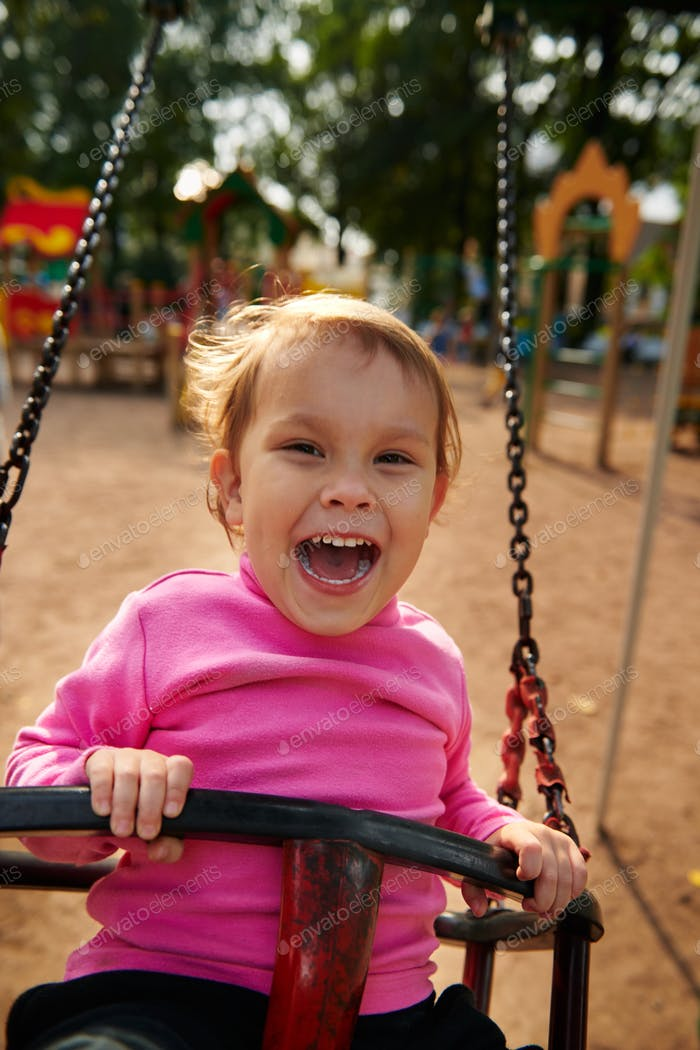 Little girl with funny facial expression swinging on the swings